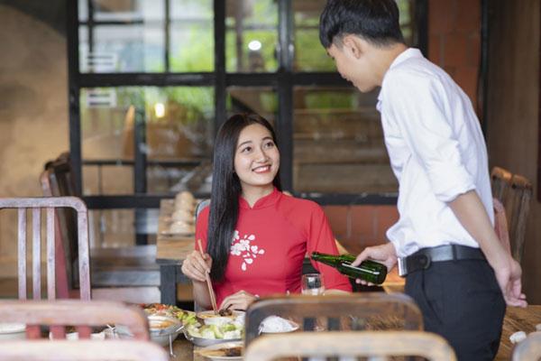女性に粋な会話をしてビールを注ぐ男性