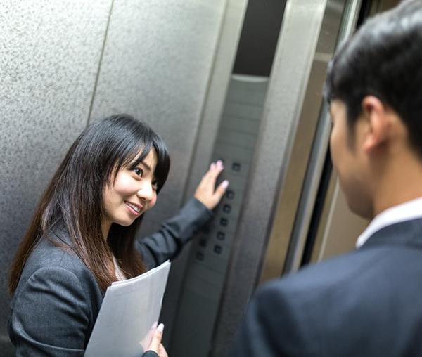 エレベーターで男性の行き先階数を尋ねる女性